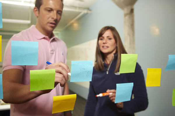 Man & woman collaborating on a sale with post-it notes to demonstrate team selling