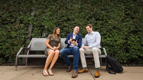 Photograph of three people on a park bench