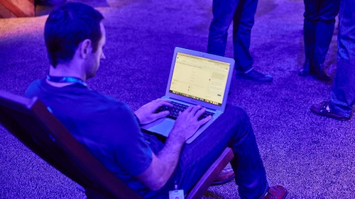 Photo of a man with a laptop in conversation with a bot