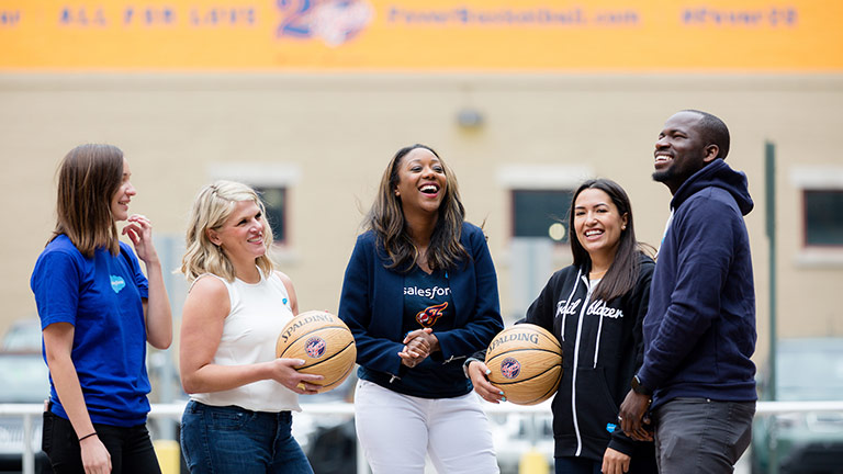 Kai Johnson laughing with colleagues on a basketball court