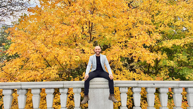 Johnny Silva sitting on a fence in the fall